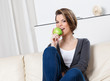 Sitting on the sofa attractive woman eats a green apple
