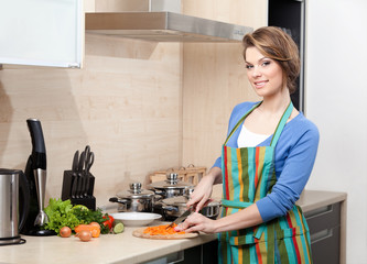 Pretty woman in striped apron cooks in the kitchen
