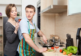 Man in apron slices vegetables for dinner for his girlfriend