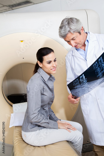 Radiologist Showing X-ray To Female Patient