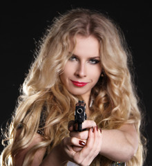 Sexy  blond woman holding gun isolated on black background