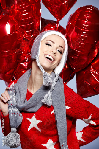 Cute young woman wearing warm winter clothing and holdingred  he