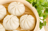 Chinese steamed buns in bamboo steamer basket with cilantro on w