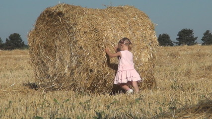 Little Girl Pushing and Playing with a Bale of Straw