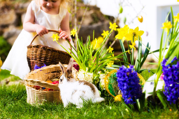 Easter Bunnies on meadow with basket and eggs