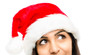 Close up of pretty woman wearing christmas hat looking up isolat