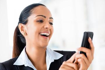 Closeup portrait of beautiful Indian businesswoman sending text
