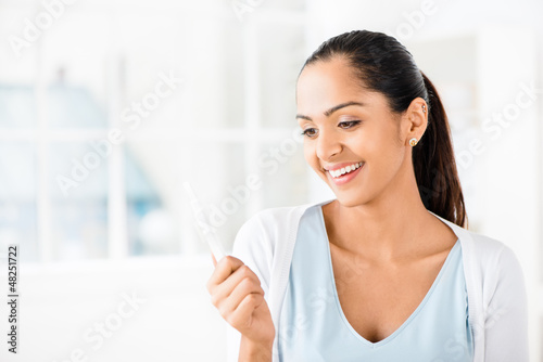 Happy Indian woman taking pregancy test