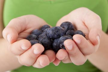 Beautiful woman eating blueberries