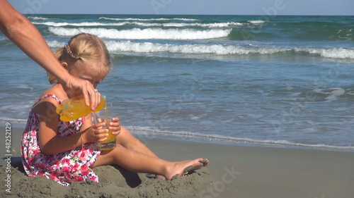 Little Girl Drinking Juice on Beach