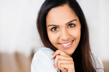 Closeup portrait of attractive indian young woman smiling at hom