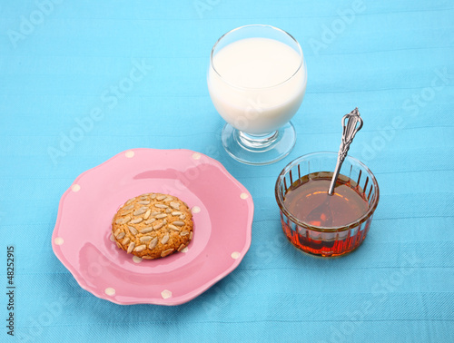 pink plate with sunflower seed cookie with honey and milk