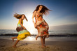 Mother and daughter dancing on beautiful beach.