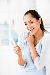 Happy Indian woman taking pregnancy test