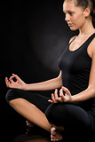 Relaxed young woman exercising in lotus position