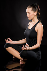 Full length of a young woman meditating