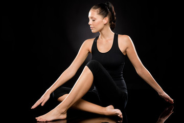 Young woman performing yoga with stretched arms