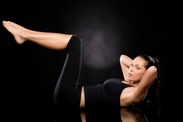 Young woman doing stretching exercise on floor
