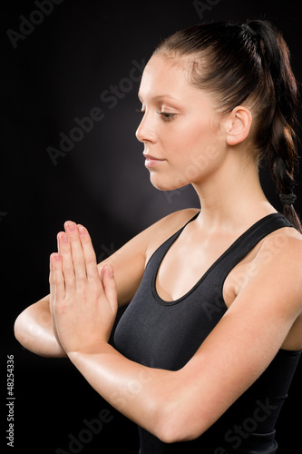 Tranquil woman performing yoga with eyes closed