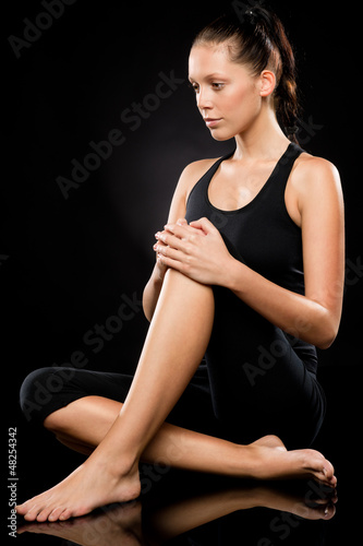 Sporty brunette woman relaxing while doing yoga