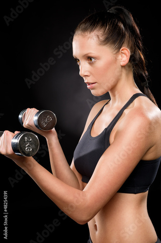 Pretty young woman lifting dumbbells in sportswear