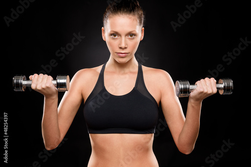 Portrait of a sporty woman lifting weights
