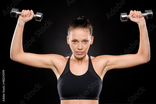 Brunette woman lifting dumbbells over her head