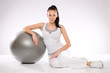Young Caucasian woman leaning on fitness ball