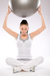 Woman holding fitness ball above her head