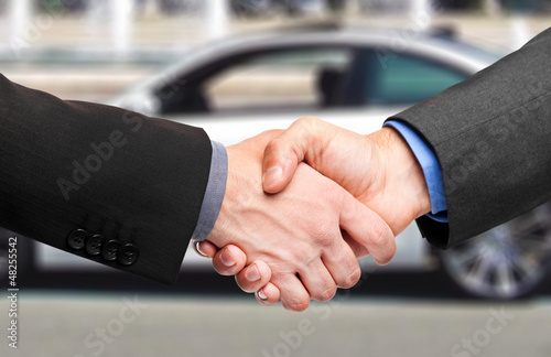 Two men shaking hands after a successful car purchase