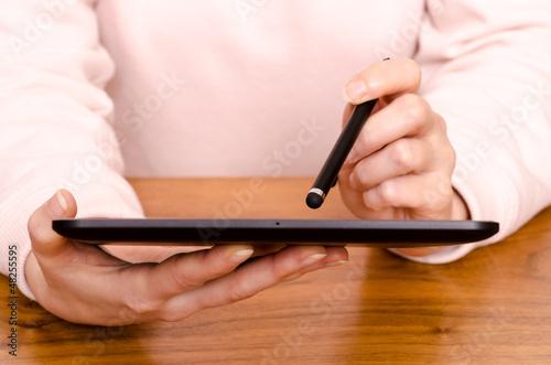 Hände einer Frau mit Stift und Tablet Computer