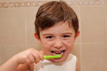 Cute boy washing his teeth