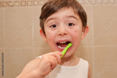 Cute boy washing his teeth