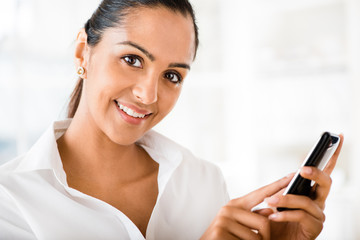 Indian business woman using mobile phone happy