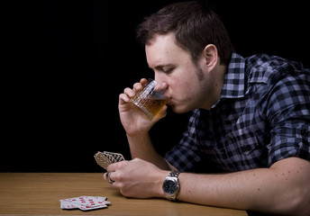 man playing cards drinking whisky