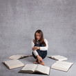 Young girl studying surrounded by books against grey background.