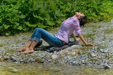 Frau bem Entspannen am Flussbett