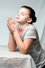 An image of a young girl praying on white background