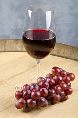 Glass of Red Wine and Bunch of Grapes on a Barrel