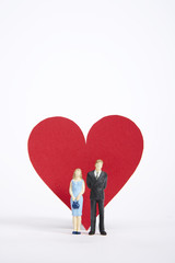 Figurine of couple standing in front of heart shape