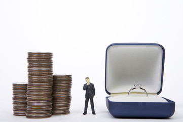 Businessman figurine standing between coins and ring box
