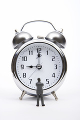Businessman figurine standing and looking at alarm clock
