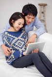 Young Asian couple using pad PC