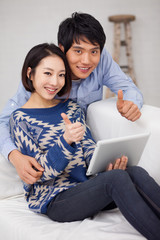 Young Asian couple using pad PC and show thumbs