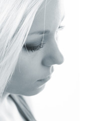 Profile of the beautiful sad girl with long blond hair