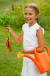Vegetable garden - lovely girl with bunch of carrots
