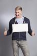 Joyful man giving thumbs up at blank signboard.