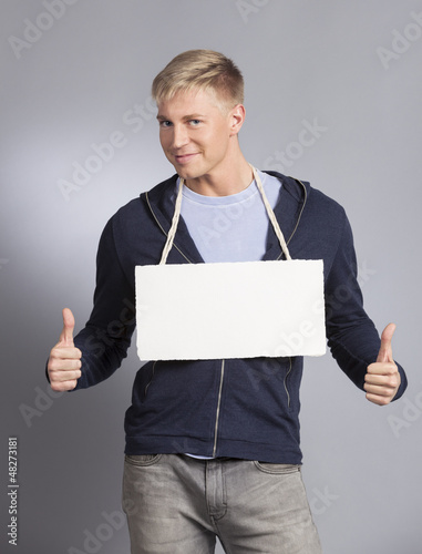 Joyful man giving thumbs up at empty signboard.