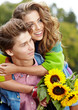 Loving young man hugging his girlfriend with sunflowers in their