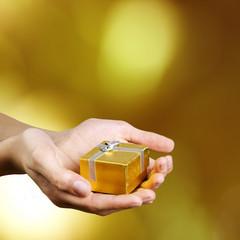 mano con caja de regalo dorada